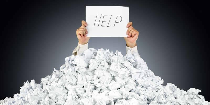 Persoon bedolven onder proppen papier met in de hand een papier met het woord help erop, dit verwijst naar de vraag om bouwbegeleiding